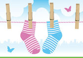 Vector illustration of a line with clothespins and baby socks. — Wektor stockowy
