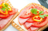 Fresh appetizing sandwiches with pork tenderloin, cheese, tomato, pepper and parsley sprig arranged in ceramic plates . — Stock Photo