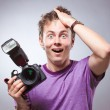 Excited surprised photographer with camera at hand - Stock Photo