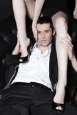 Portrait of attractive young man embracing womans perfect legs — Stock Photo