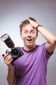 Excited surprised photographer with camera at hand — Stock Photo