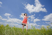 Beautiful young woman standing on field enjoying wind — Stock Photo