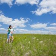 Loving dreamy couple on summer field embracing - Stock Photo