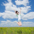 Jumping happy young brunette women on summer field — Stock Photo