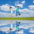 Jumping happy couple on field with reflection in the water — Stock Photo