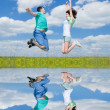 Jumping happy couple on summer field  with reflection in the wat — Stock Photo