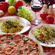 Classic Italian food setting with pizza, pasta, salad and wine - Stock Photo