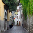 Stock Photo: View of narrow street in Arco, North Italy, with Alps in background