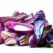 Stock Photo: Pile of female violet shoes isolated on white background