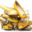 Stock Photo: Pile of female yellow shoes isolated on white background