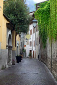 View of a narrow street in Arco, North Italy, with Alps in the background — Stock Photo