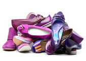 Pile of female violet shoes isolated on white background — Stock Photo