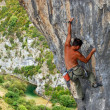 Stock Photo: Rock climber moving up rock