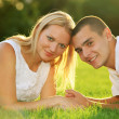 Young happy couple lying down on grass — Stock Photo