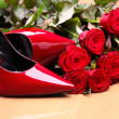 Stock Photo: Close-up of pair of red female shoes and red roses