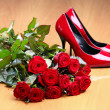 Stock Photo: Bunch of red roses and pair of red female shoes