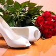 Pair of white female shoes and bunch of red roses - Stock Photo