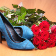 Pair of blue female shoes and bunch of red roses — Stock Photo