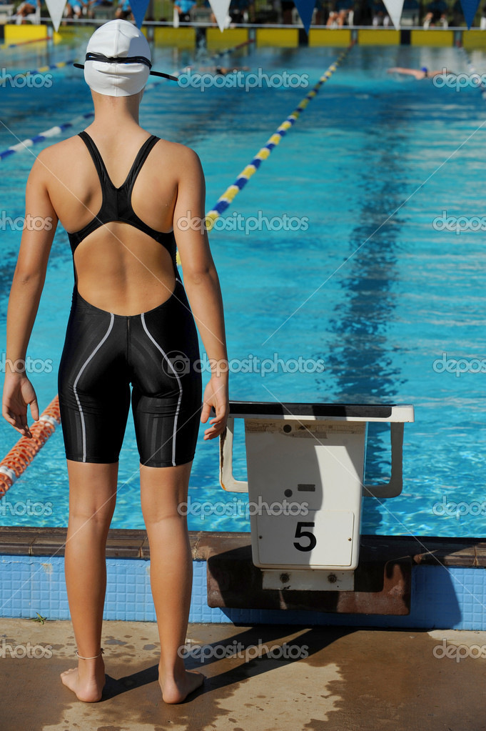 A female relay swimmer waits for her turn to start during a competition.  Stock Photo #3528167