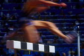 Legs and feet of female runners during a woman's hurdle competition — Stock Photo