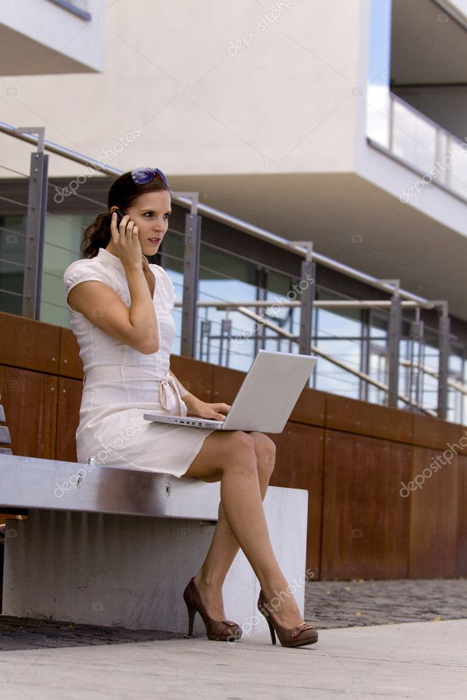 Young woman with notebook and moile phone in front of a modern office buidling — Stock Photo #3502744