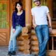 Young couple in front of a wooden house — Stock Photo