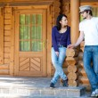 Young couple in front of a wooden house — Stock Photo #3555779