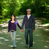 Young couple walking through forest — Stock Photo