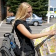The girl-traveller with a map of the city and a backpack — Stock Photo #3630894