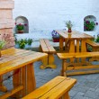 Wooden tables with flowers and benche — Stok fotoğraf