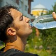 The young man drinks water from a plastic bottle — Stock Photo #3631242