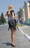 The girl-traveller with a backpack in the street — Stock Photo
