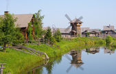 Village with a windmill about river — Stock Photo