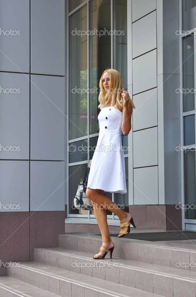The girl comes downstairs from shop with bag in hand — Stock Photo #3631065