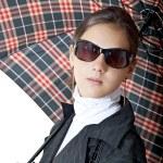 Girl in sun glasses and raincoat under umbrella — Stock Photo #3778708