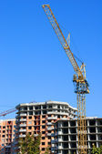 The elevating crane and buildings — Stock Photo