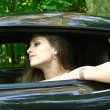 The beautiful girl is looking from the sport car — Stock Photo