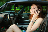 Beautiful girl is talking on telephone in the black auto — Stock Photo