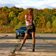 Sexual bright girl is standing in front of the sport black car - Stock Photo