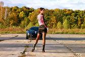 Verleidelijke jonge vrouw in shot rok in de buurt van sport auto. natuur. — Stockfoto