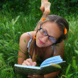 Beautiful girl in the grass smiles and writes in a notebook — Stock Photo #3608632