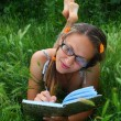 Beautiful girl in the grass smiles and writes in a notebook - Stock Photo