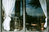 Antique oil lamp, coffee mill and kettle at window-sill — Stock Photo