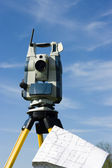 Theodolite and a map — Stock Photo