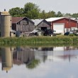 Old farm reflected - Stock Photo