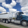 Blurred semi-truck under crazy clouds - Stock Photo