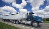 Camión semi borrosa bajo nubes locas — Foto de Stock