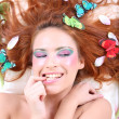 Young red-haired woman with butterflies and petals — Stock Photo