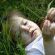 Nice small girl lays on green grass — Stock Photo
