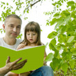 Father and daughter reading a book on nature — Foto de stock #3866778